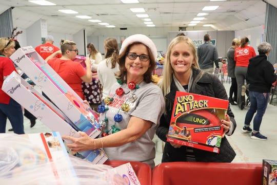 Sue Whittington and Morgan Murphy, members of LEADERship Martin County Alumni, help sort toys in preparationfor the 2018White Doves distribution days.
