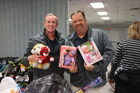 Ryan Strom and Brett Zurich, members of LEADERship Martin County Alumni, help sort toys in preparationfor the 2018White Doves distribution days.