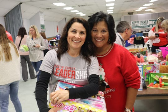 Tara Zweben and Carol Houwaart-Diez help sort toys in preparation for the 2018 White Doves distribution days.