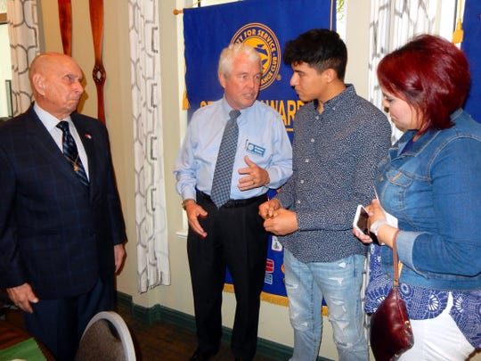 Charles G. Read, left, and Andrew Molloy discuss what it means to be a Marine with Jesse Zuniga while his mother, Chriselda Carrillo, looks on at a recent meeting of the Exchange Club of Indian River.