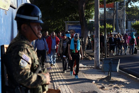 Police stand by as locals begin their journey north toward the U.S. border, during a migrant caravan passing through the capital of San Salvador, El Salvador, early Wednesday, Jan. 16, 2019. Migrants fleeing Central America's Northern Triangle region comprising Honduras, El Salvador and Guatemala routinely cite poverty and rampant gang violence as their motivation for leaving.