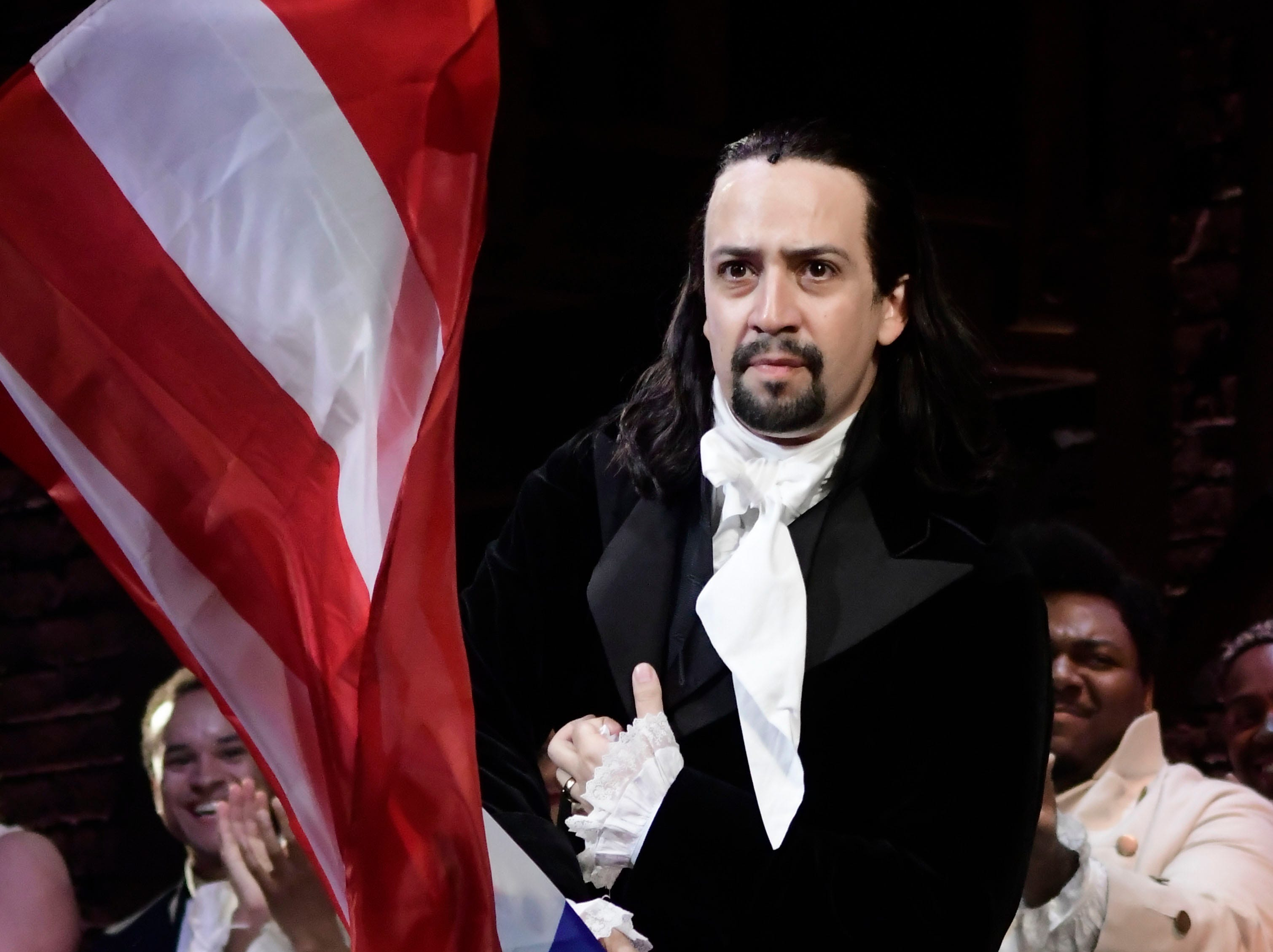 "Lin-Manuel Miranda, creator of the award-winning Broadway musical, ""Hamilton,"" proudly waves a Puerto Rican flag after receiving a standing ovation at the end of the play's premiere held at the Santurce Fine Arts Center, in San Juan, Puerto Rico, Friday, Jan. 11, 2019. The musical is set to run for two weeks and will raise money for local arts programs."