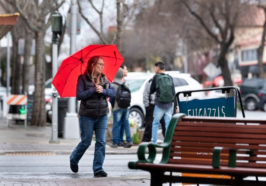 Becky Wing of Visalia crosses Locust Street in Downtown during Tuesday's rain. More rainy days are expected.