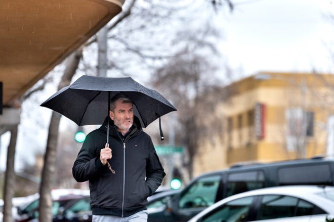David McMunn of Visalia takes a walk along Man Street in Downtown Visalia during Tuesday's rain. More rainy days are expected.