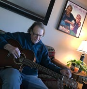 Glen Moberg tunes his guitar in his town of Maine home. The painting above his left shoulder is by his son, Thomas Moberg. It's of him pulling Thomas away from a fire during a camping trip.