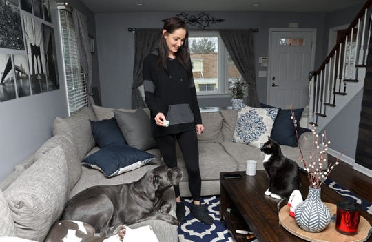 Nicole Morandy, 29, plays catch with her cat Ziggy as her dogs sit close-by at home in White Plains Jan. 10, 2019. Morandy has five pets; two dogs and three cats, that she describes as her children. After one of her dogs were sick she found a more holistic approach to providing for their medical care, which includes feeding them a raw diet.