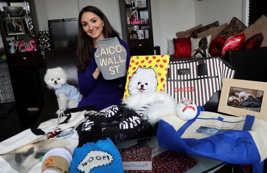 "Kris Ruby holds one of her favorite pieces of clothing for her teacup Pomeranian, Caicos, that highlights where she got him from, at their home in White Plains Jan. 10, 2019. Ruby, 32, describes Caicos as the ""love of her life"" and gives him the very best treatment in everything from gourmet pet food to personalized accessories."