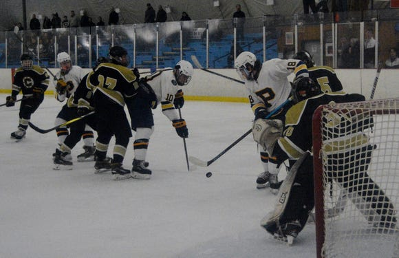 Pelham forwards Andrew Shulzhenko (10) and Anthony Rosa (18)  scramble to corral the puck and get a shot on goal during the first period of the Pelicans' 7-1 win  over Clarkstown on Tuesday,  January 15,  2019 at the Ice Hutch in Mount Vernon.
