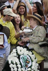 Jockey John Velasquez and owner Phyllis Wyeth hold the trophy after Union Rags won the Belmont Stakes on June 9, 2012, at Belmont Park in Elmont, N.Y.