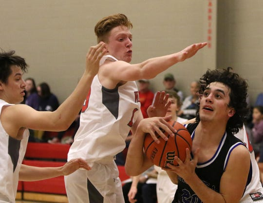 Wichita Christian's Evan Findley gets the ball while guarded by Christ Academy's Carson Kosub, left, and Grayson Southard Tuesday, Jan. 15, 2019, at Christ Academy.