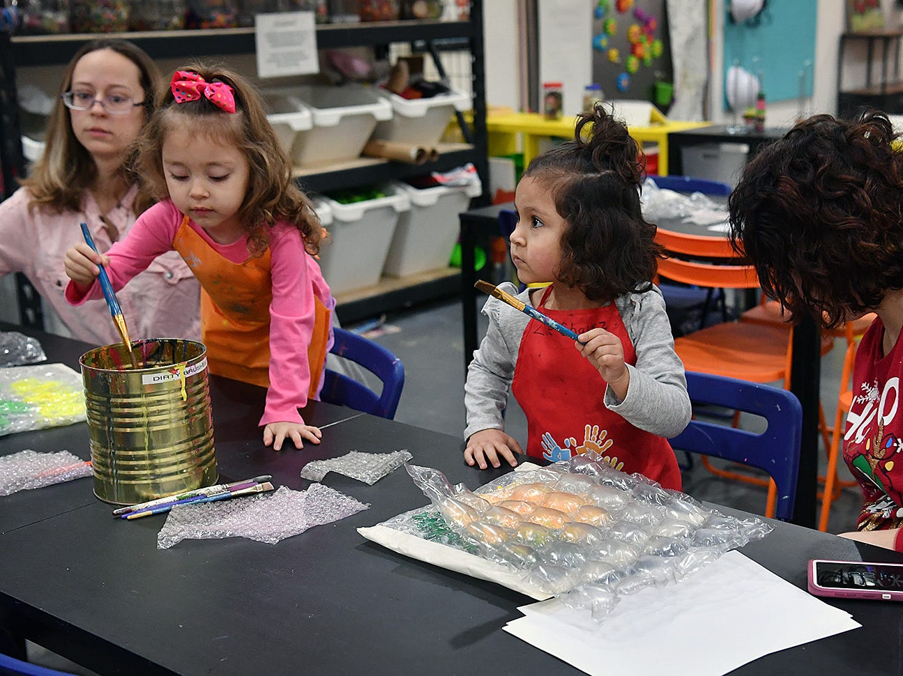 Dessirae Perez, left, her daughter, Aurora, Zoe Chavez and her mother, Tiffany Chavez, participate in a bubblewrap and paint art experience at CrashWorks STEAM Studio & Makerspace Wednesday.