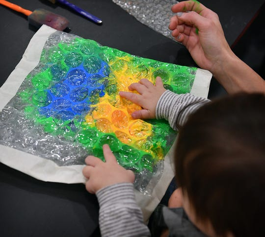 A child squishes paint around inside a bubblewrap envelope during a Mommy and Me art program at CrashWorks STEAM Studio & Makerspace Wednesday morning.