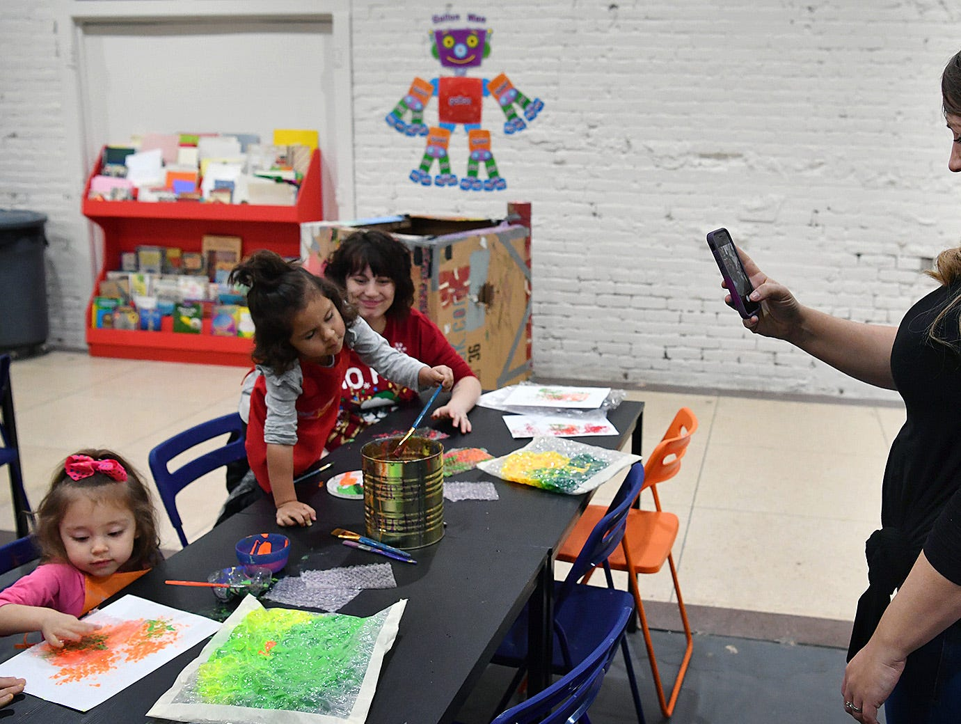 Shauna LaRocque, owner of CrashWorks STEAM Studio & Makerspace, takes photos for social media during a Mommy and Me event using bubblewrap and paint.