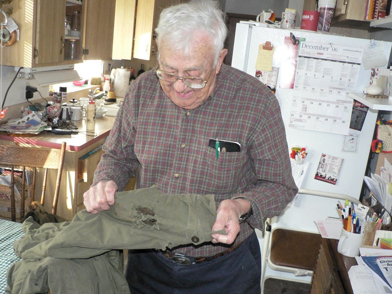 Milt Sunde, longtime poultry expert at the UW-Madison surveys the shrapnel holes in his army jacket that he was wearing when shells exploded nearby.  He survived World War II unhurt.
