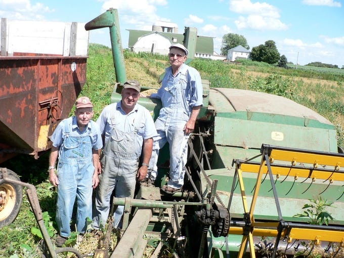 Eighty-year old Vernon Dunn (left), his son, Donald, both of Oregon, Wis. and his 84 year old brother, Gerald Dunn, Fitchburg, Wis (right), get ready to combine in 95 degree heat in the summer of 2005.