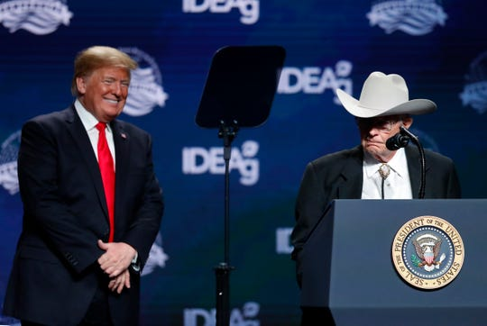President Donald Trump watches as jim Chilton, a rancher from the Arizona, speaks at the American Farm Bureau Federation convention in New Orleans, Monday, Jan. 14, 2019.