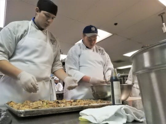 Branson Umensetter and Andrew Sceurman prepare chicken for a jambalaya.