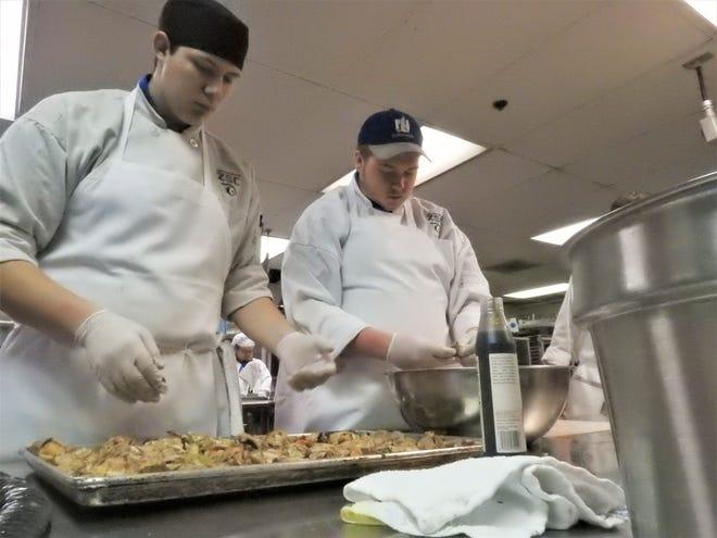 Branson Umensetter and Andrew Sceurman prepare chicken for a jambalaya.
