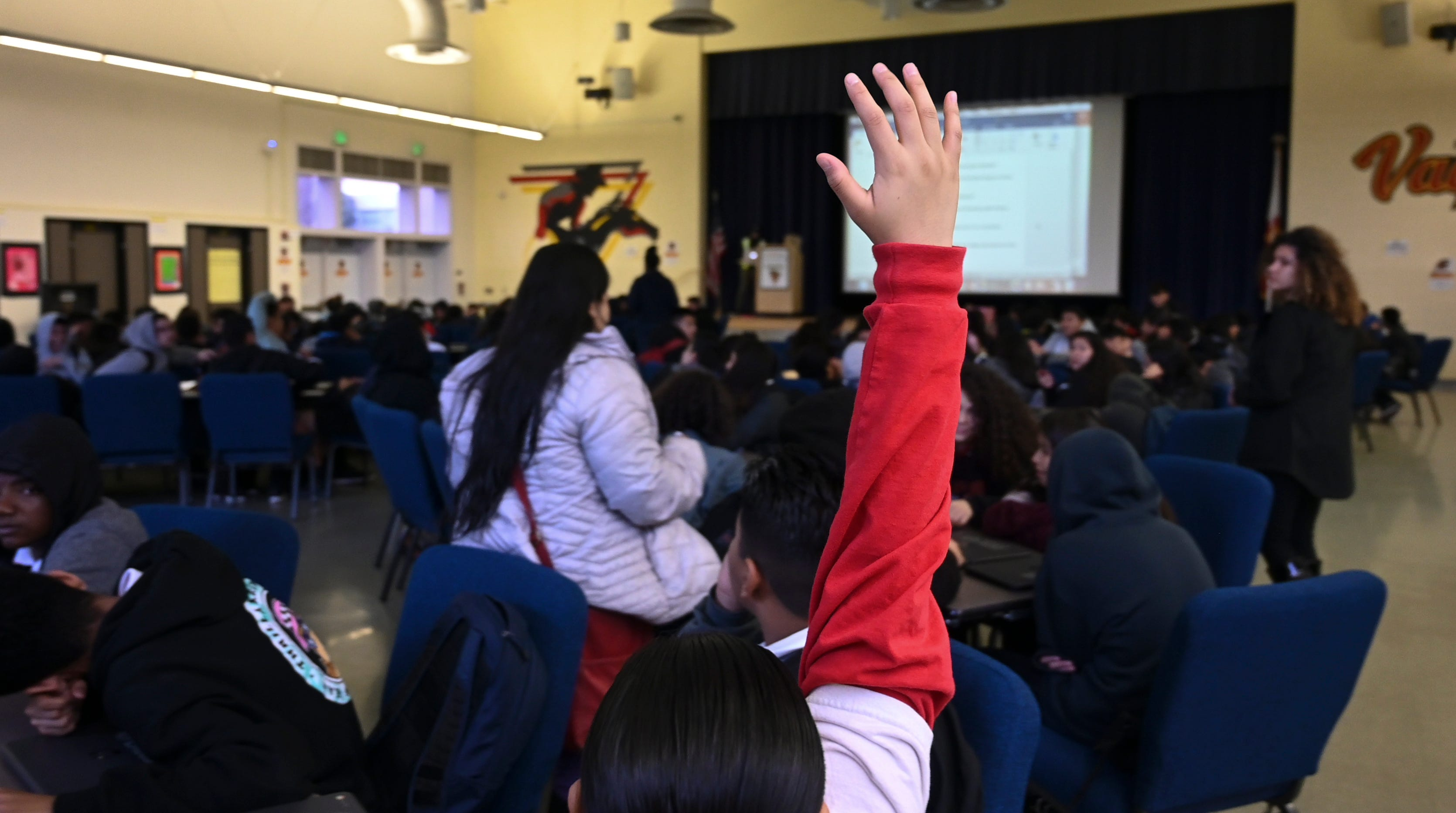 A student raises her hand to answer a question in a class held in the multipurpose room at Vista Middle School in Los Angeles. The 30,000 members of United Teachers Los Angeles went on strike Monday.