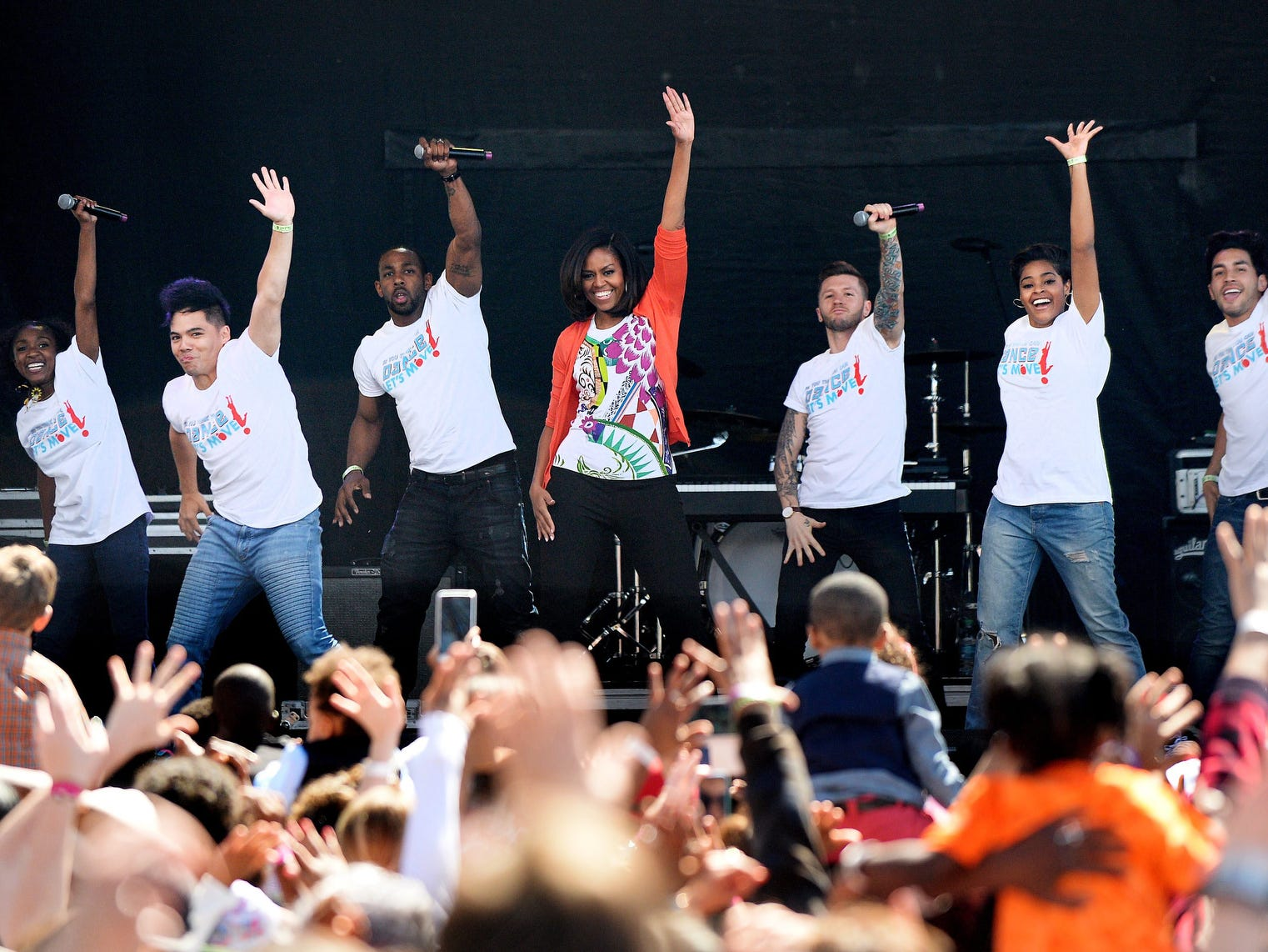 """epa04693774 US First Lady Michelle Obama (C) dances with members of the All Stars from from the television show 'So You Can Dance' during the 137th annual White House Easter Egg Roll on the South Lawn of the White House in Washingon DC, USA, 06 April 2015. The Easter egg roll falls on the fifth anniversary of Michelle Obama's Let's Move initiative to combat childhood obesity. The first lady asked Americans of all ages to """"give me five ways they are leading a healthier life,"""" and to participate on Twitter and other social media websites by using #gimmefive.  EPA/Olivier Douliery / POOL"""