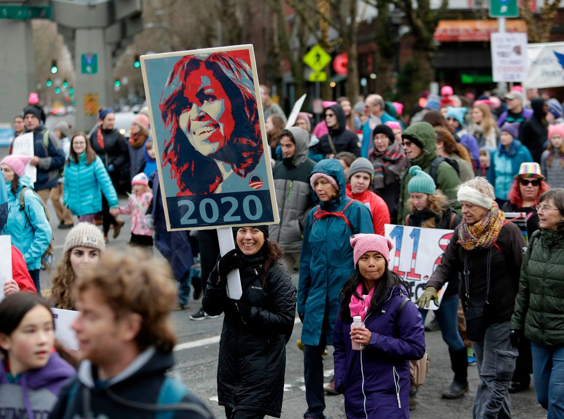 A woman carries a sign with former First Lady of the United States Michelle Obama at the Women's March 2.0, one year after women worldwide marched for women's rights and to protest US President Donald Trump's inauguration, in Seattle, Washington on January 20, 2018.  / AFP PHOTO / Jason RedmondJASON REDMOND/AFP/Getty Images ORG XMIT: Crowds Ra ORIG FILE ID: AFP_XA4N9
