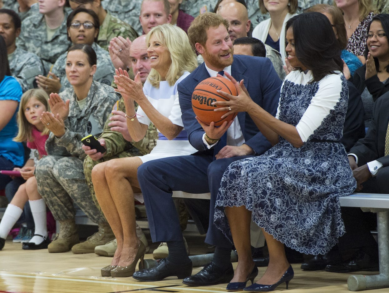 Britain's Prince Harry hands a basketball to US First Lady Michelle Obama(R) alongside Jill Biden, wife of the US Vice President, as they watch a Wounded Warriors wheelchair basketball game at Fort Belvoir, Virginia, October 28, 2015. The Prince, who is the Patron of the Invictus Games, an international sports competition for wounded armed service members, visits to highlight the upcoming Invictus Games to be held in Orlando in May 2016. AFP PHOTO / SAUL LOEBSAUL LOEB/AFP/Getty Images