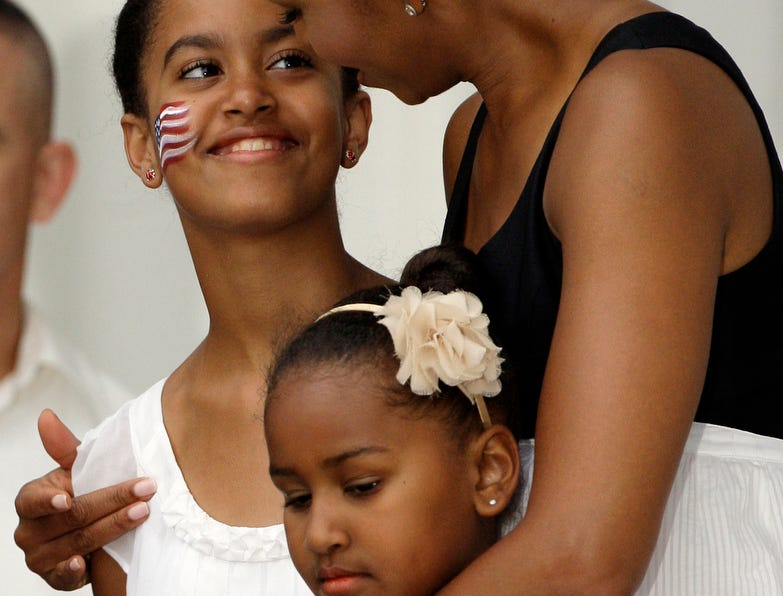 FILE - In this July 4, 2009, file photo, Michelle Obama, right, talks with her daughter Malia Obama, left, who is 11 today, as she holds her daughter Sasha Obama, 7, on the White House balcony as President Barack Obama addresses guests below during a Fourth of July party for members of the United States armed services and their guests on the South Lawn in Washington. (AP Photo/Alex Brandon, File) ORG XMIT: WXSC503