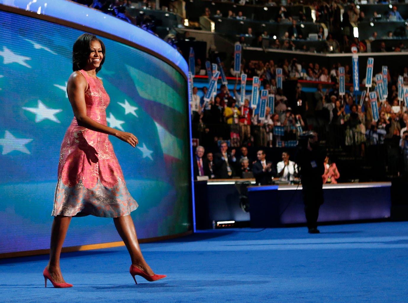 FILE - In this Sept. 4, 2012 file photo, first lady Michelle Obama, dressed in a Tracy Reese pink silk jaquard dress, walks on the stage at the Democratic National Convention in Charlotte, N.C. Reese, who hails from Detroit, is clearly one of the first lady's favored designers as Obama has been photographed in her clothes between 20 and 30 times. (AP Photo/Jae C. Hong, File) ORG XMIT: WX431