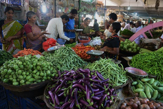 Shoppers buy vegetables at a farmers' market on World Food Day in Hyderabad, India, on Oct. 16, 2014.