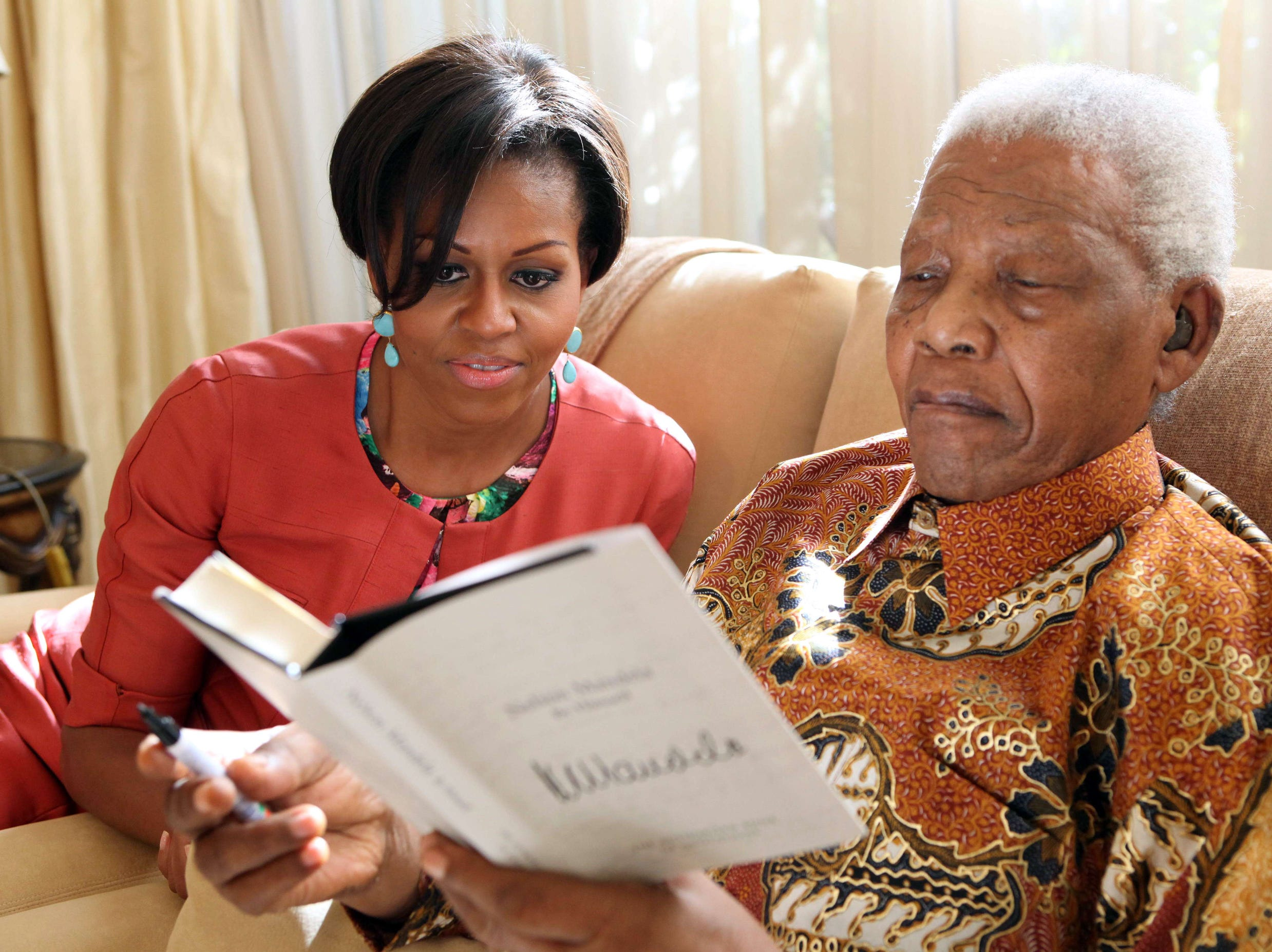 """RESTRICTED TO EDITORIAL USE - MANDATORY CREDIT """"AFP PHOTO / NELSON MANDELA FOUNDATION / DEBBIE YAZBEK"""" - NO MARKETING NO ADVERTISING CAMPAIGNS - DISTRIBUTED AS A SERVICE TO CLIENTS Handout photo provided by the Nelson Mandela Foundation shows former South African President Nelson Mandela (R) showing a book to US First Lady Michelle Obama at his home in Johannesburg on June 21, 2011. US First Lady Michelle Obama visited former South African president Nelson Mandela at his home on June 21 during the first full day of a six-day visit to southern Africa, his foundation said. Obama, who arrived in South Africa late June 20, visited Mandela's charitable foundation and archives Tuesday and took a tour with the Nobel Peace Prize winner's wife, the humanitarian and former Mozambican first lady Graca Machel.   AFP PHOTO / Debbie Yazbek/ Nelson Mandela FoundationDEBBIE YAZBEK/AFP/Getty Images ORG XMIT: - ORIG FILE ID: 521136023"""