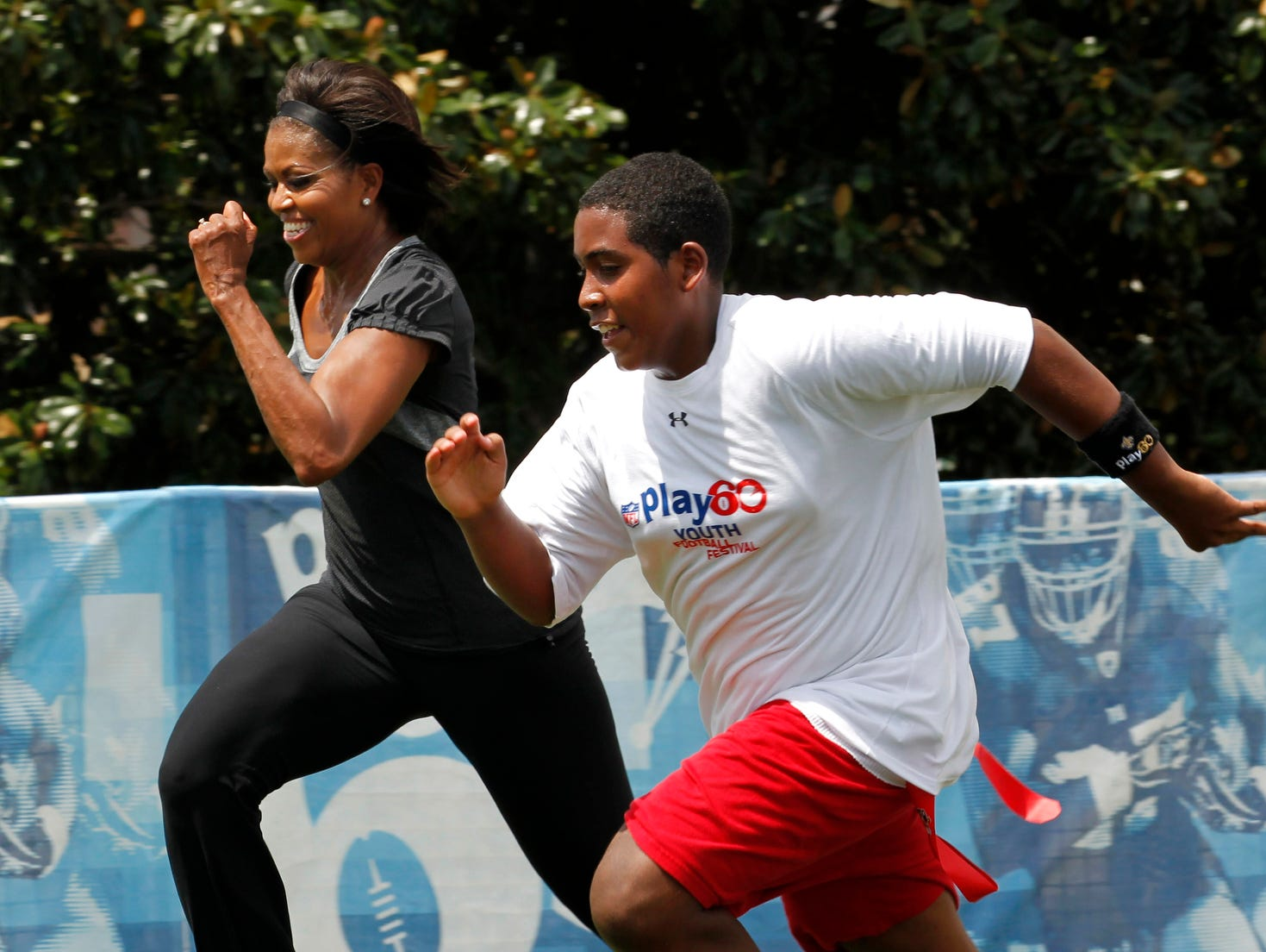 """FILE - In this Sept. 8, 2010, file photo, first lady Michelle Obama runs a 40-yard sprint as she participates in the Let's Move!  Campaign and the NFL's Play 60 Campaign festivities with area youth, to promote exercise and fight childhood obesity in New Orleans. Michelle Obama has a new look, both in person and online, and with the president's re-election, she has four more years as first lady, too. The first lady is trying to figure out what comes next for this self-described """"mom in chief"""" who also is a champion of healthier eating, an advocate for military families, a fitness buff and the best-selling author of a book about her White House garden. For certain, she'll press ahead with her well-publicized efforts to reduce childhood obesity and rally the country around its service members. (AP Photo/Gerald Herbert, file) ORG XMIT: WX111"""