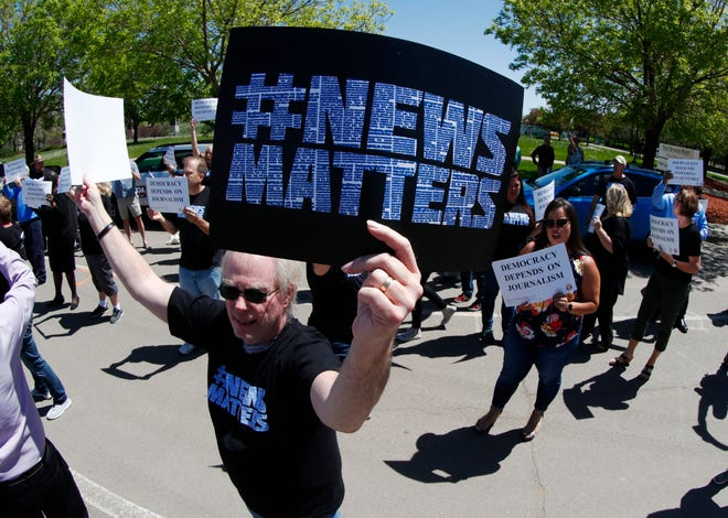 Gene Forbes, who works in the pre-press department of The Denver Post, holds up a placard during a rally against the paper's ownership group, Alden Global Capital,  May 8, 2018, outside the paper's office and printing plant in north Denver. Members from all guild units were on hand in Denver for the rally at which they urged Alden Capital to invest in the newspapers that it controls or sell the properties.