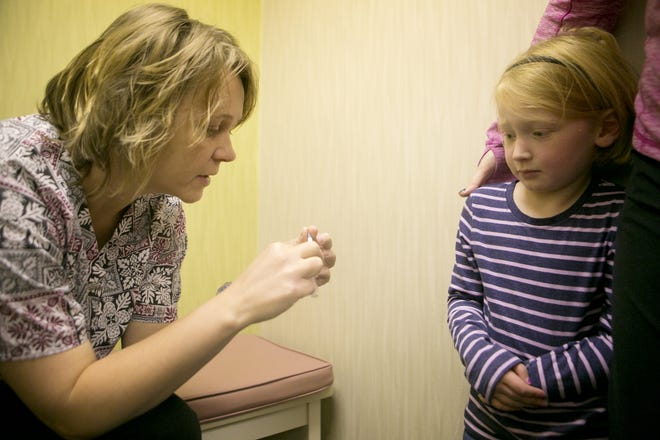 Medical assistant Tiffany Lemmer, left, explains to Maggie McNamara of Spencer, 4, center, whats going to happen when she receives the MMR vaccine at the Marshfield Clinic, on Nov. 17, 2014. Not pictured, Maggie McNamara's mother, Stephanie McNamara, right. The Marshfield Clinic is researching the effectiveness of the third dose in adults.