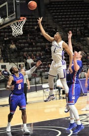 ACU's Jaren Lewis (1) tips in a teammate's missed 3-pointer while Houston Baptist's Ian DuBose (0) and Edward Hardt look on. Lewis' tip-in tied the game at 63 with 3:37 left in the game. ACU beat the Huskies 75-68 in the Southland Conference game Wednesday, Jan. 16, 2019, at Moody Coliseum.