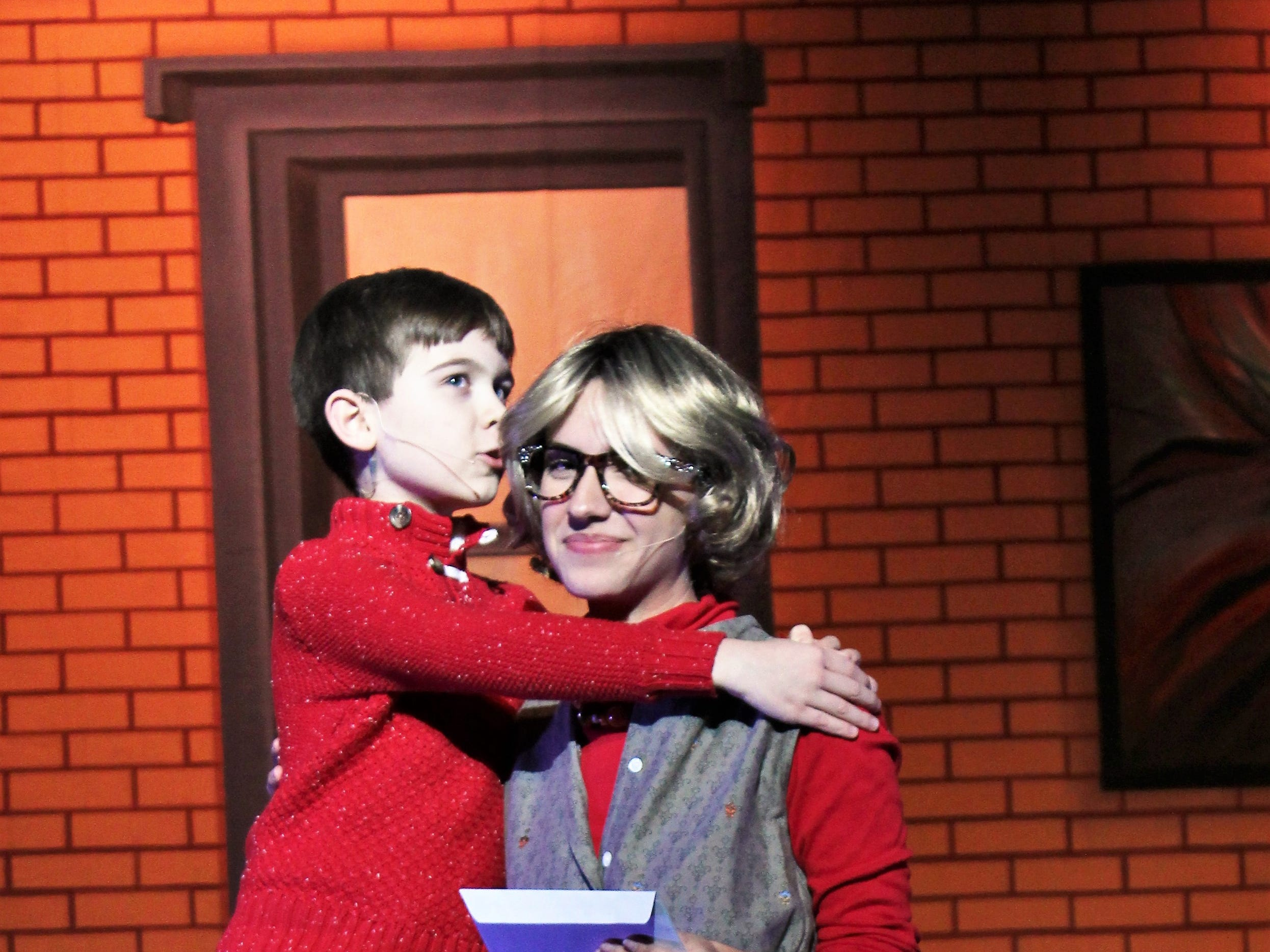 "Michael Hobbs (Phoenix Lowe) kisses his mother Emily (Mary Moore) after they write a letter to Santa at the behest of Buddy, the newest member of their family in this ""Elf, the Musical, Jr."" rehearsal scene."