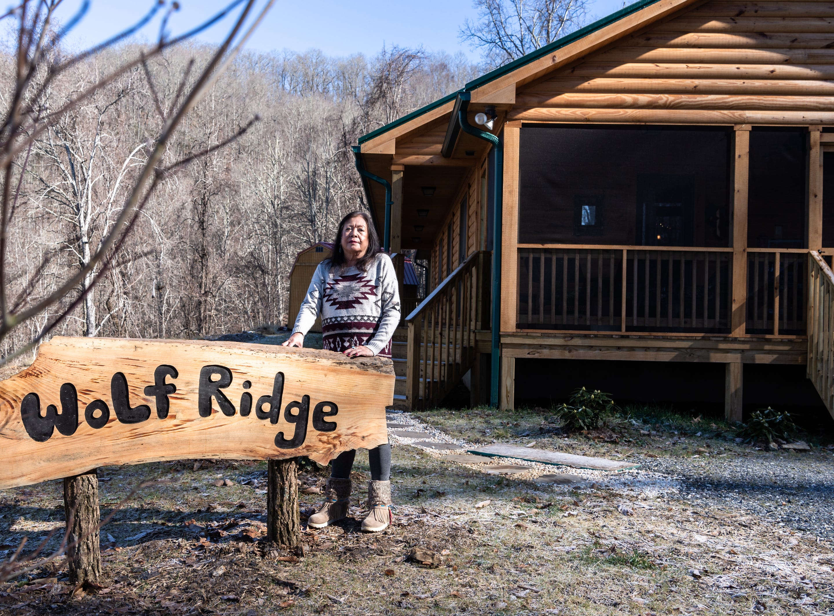 Vangie Stephens outside her log cabin home she designed in Cherokee where she lives with her husband Tommy Stephens.