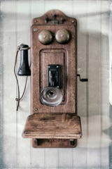 An antique wall telephone with a hand crank.
