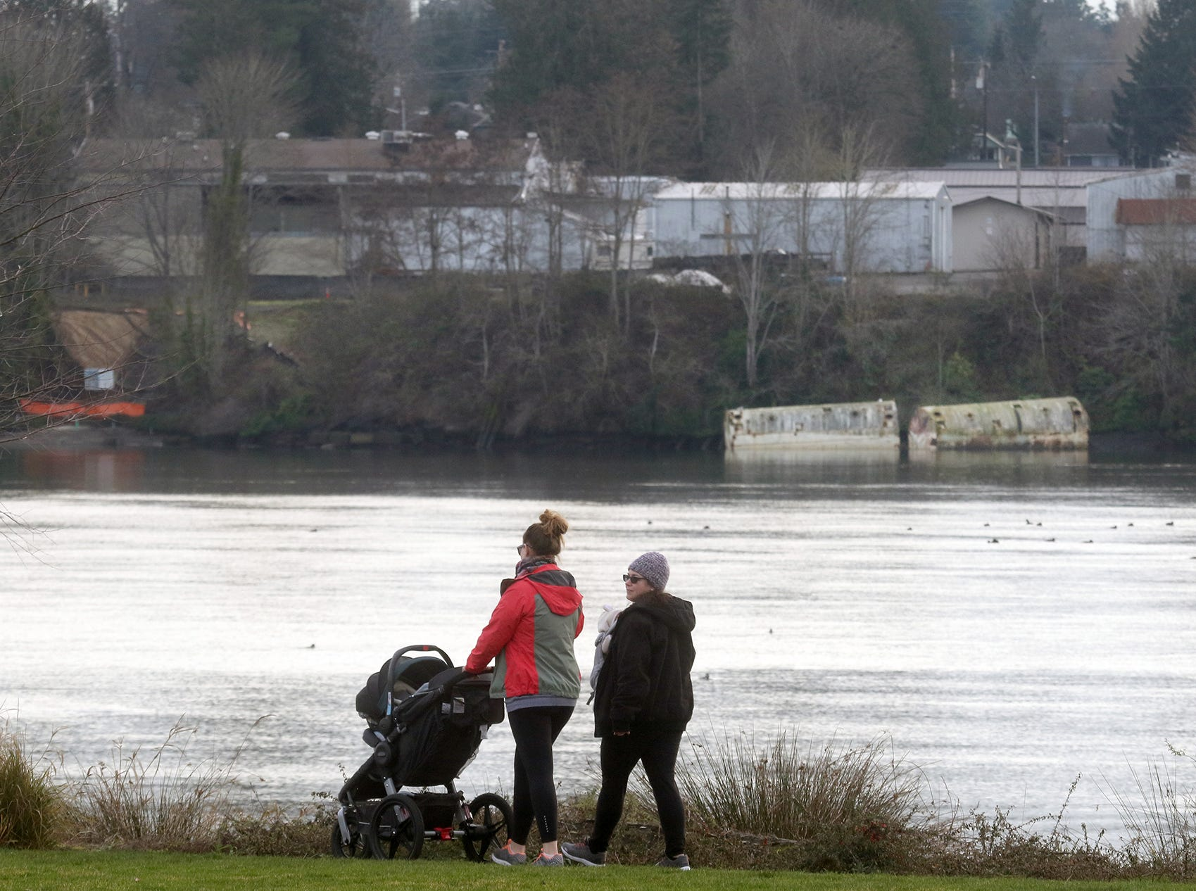 A pair of path walkers at Lions park across the water from the two ballast tanks at the north end of the Penn Plaza property that are resting on the beach in West Bremerton on Wednesday, January, 16, 2019.