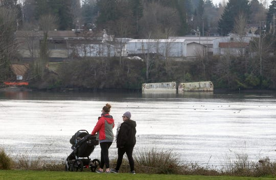 A pair walk at Lions Park, which is across the water from two ballast tanks at the north end of the Penn Plaza property in West Bremerton.