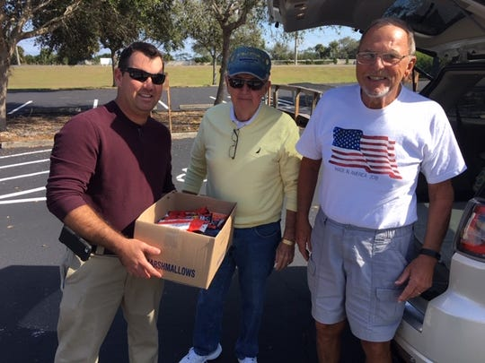 FLORIDA TODAY staffer Quentin Shock, left, takes a donation for Operation Gratitude from Vietnam veteran Bill Purdy and Jack Lehr.