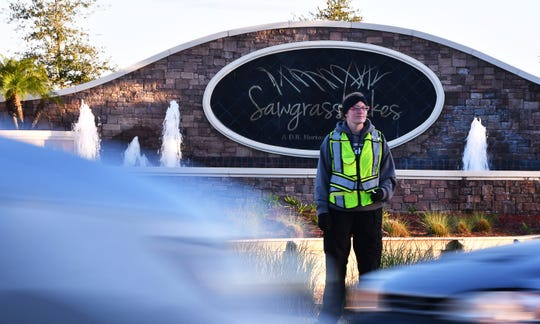 West Melbourne public safety aide Kara Lakey directs traffic from 7 to 8:15 a.m. school days at the intersection of Norfolk Parkway and Shallow Creek Boulevard in Sawgrass Lakes.