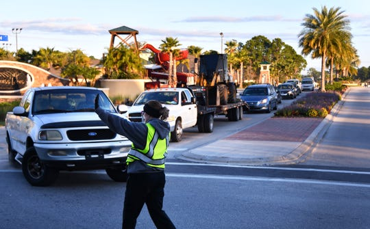 West Melbourne public safety aide Kara Lakey directs commuters Thursday morning at the intersection of Norfolk Parkway and Shallow Creek Boulevard.
