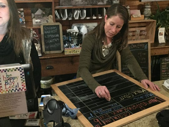Johanna Thibault, co-owner of The Den at Harry's Hardware in Cabot, updates the beer list on Jan. 12, 2019.
