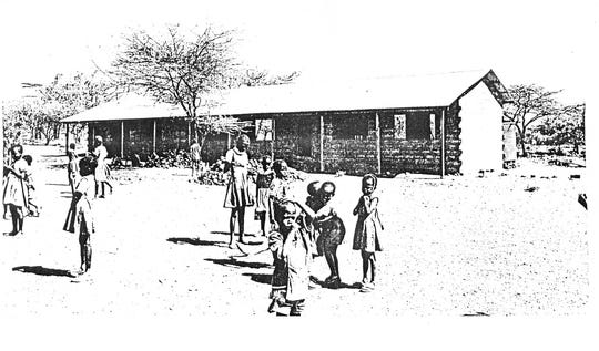 Students stand outside a the Kauma Secondary School in Kitui, Kenya, after it was built with materials funded by the Sterling High School Class of 1978.