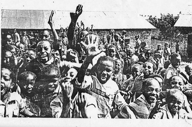 """Children in Kenya shout """"Sterling! Sterling!"""" while their photo is taken in 1978. The students were expressing gratitude for the Sterling High School Class of 1978, which funded a new school building in Kitui, Kenya, as its senior class gift."""
