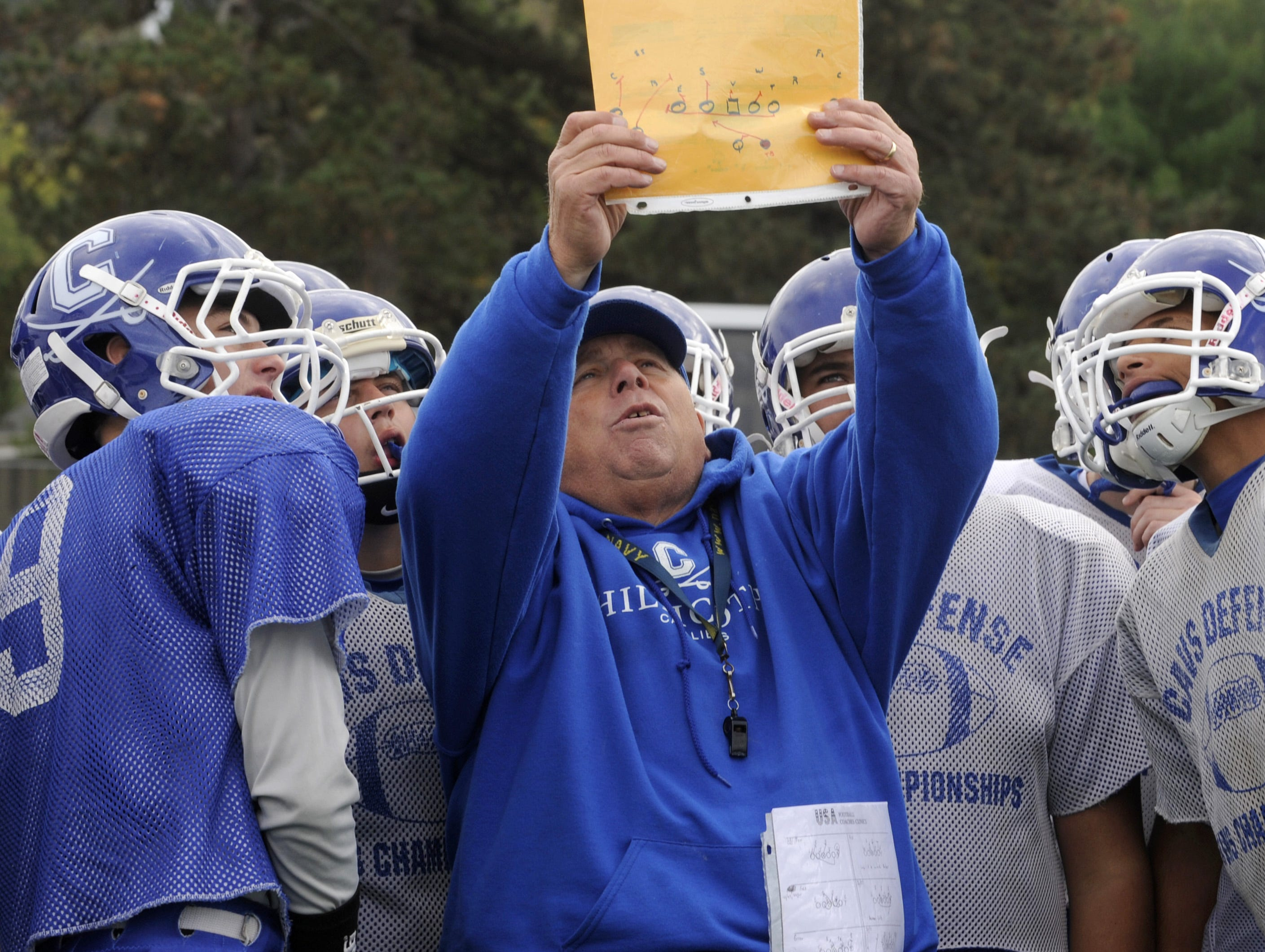 Chillicothe coach Ron Hinton reviews a play with players during an Oct. 23 practice at Herrnstein Field.