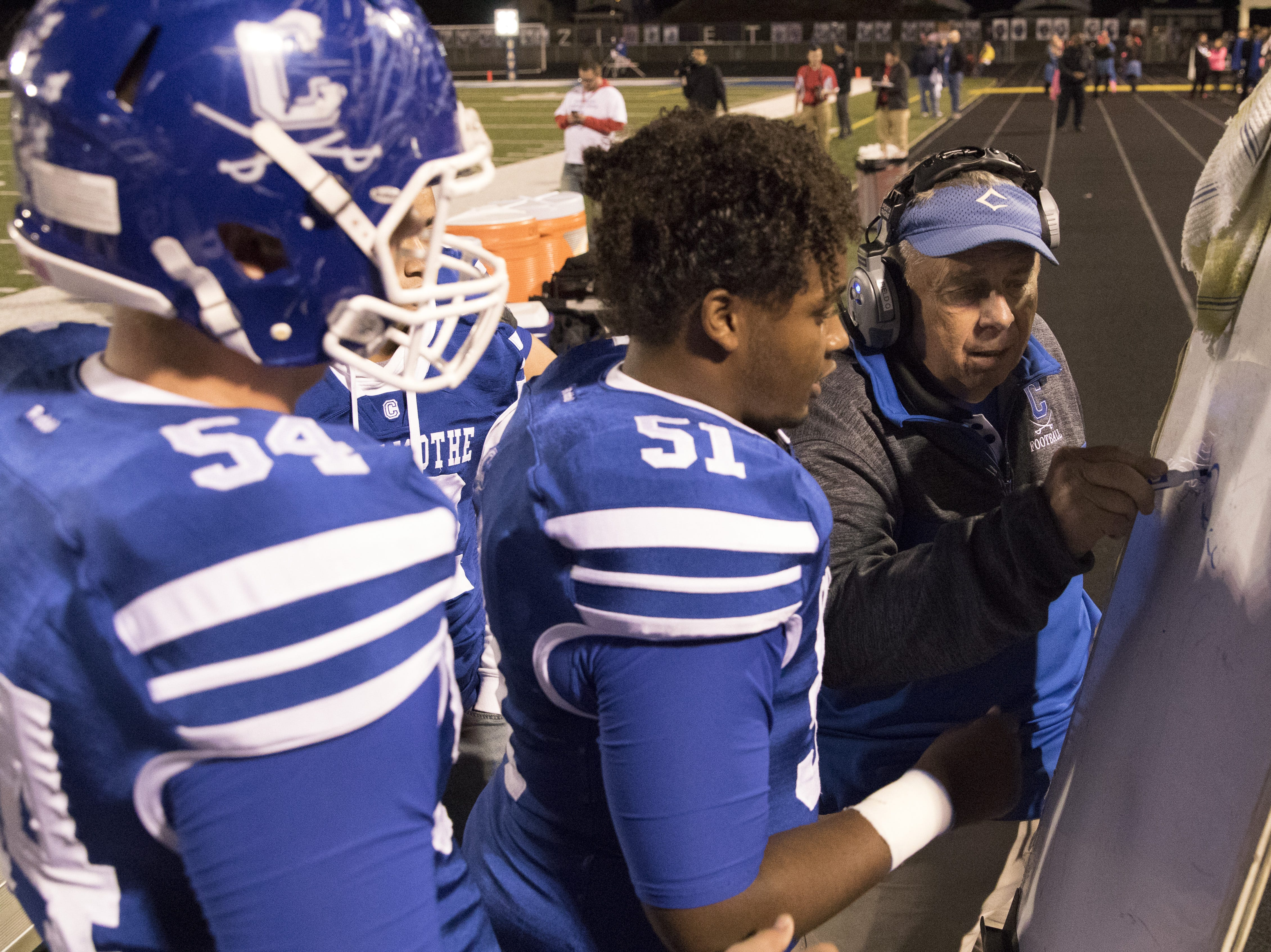 Head coach Ron Hinton talks strategy with Bryce Valentine and Bradley Rinehart during the first half of the game Friday night against Washington Courthouse.