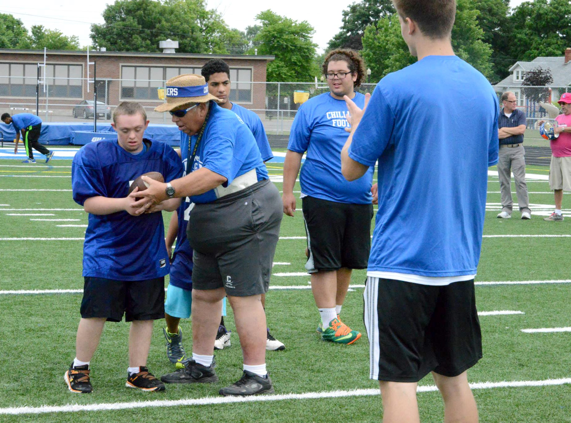 Chillicothe football coach Ron Hinton hands the ball off to Pioneer student Jacob Armstrong, during one of the drills at the Can Do Camp, between the Chillicothe football team and the Pioneer Center, at Herrnstein Field Friday.