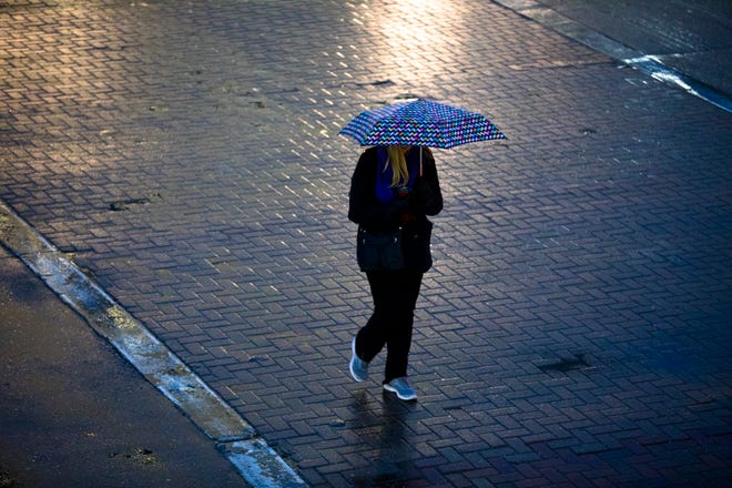Pedestrians walk in the rain in Downtown Cincinnati, on Thursday, Jan. 17, 2019.