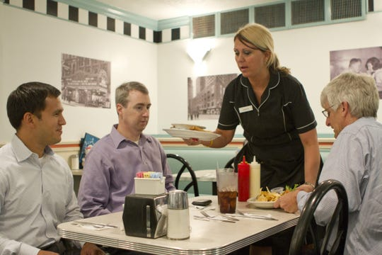 JUANITAALBRIGHT22. METRO. JUNE 22, 2011. Juanita Albright, 37, serves (left to right) Bobby Neil, 38, of Woodstock, Ga., David Kelley, 44, of Mt. Lookout and Ken Collsmith, 55, of Milford at a table in her section of Hathaway's Diner in downtown Cincinnati, Ohio on Wednesday, June 22, 2011. The Enquirer/Sam Greene